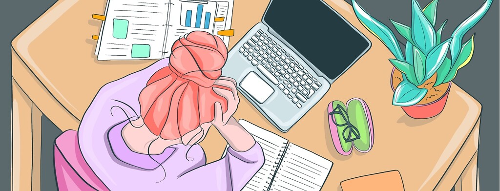 A woman staring hopelessly at her desk filled with work to do