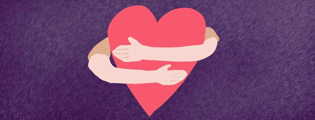Person's arms hugging a heart