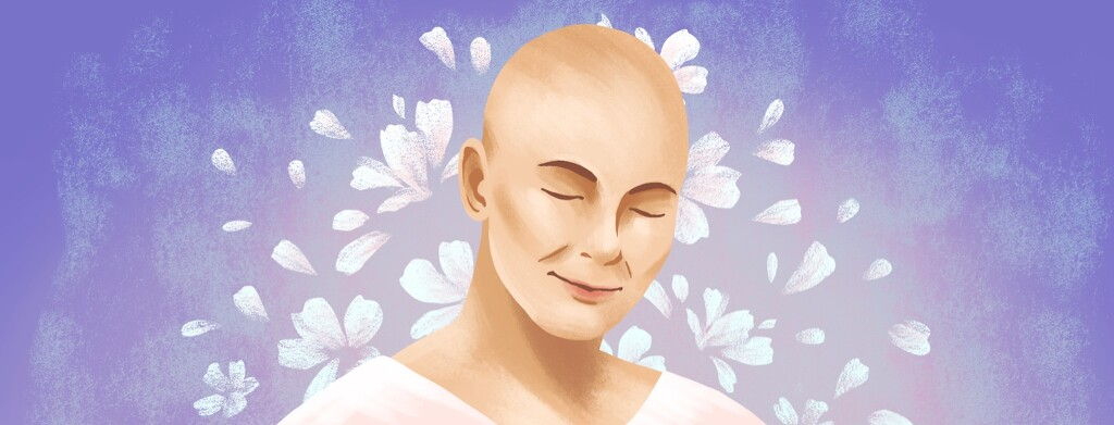 A woman with a shaved head smiles, surrounded by flowers.