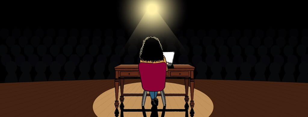 Woman at a desk with laptop computer in a spotlight on stage