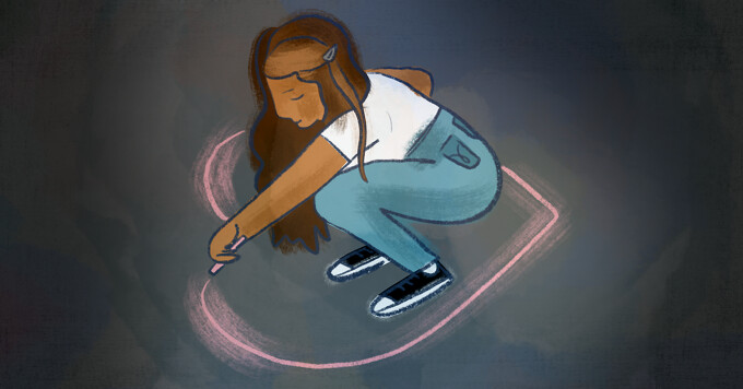 A woman crouches down and draws a heart around herself with pink chalk
